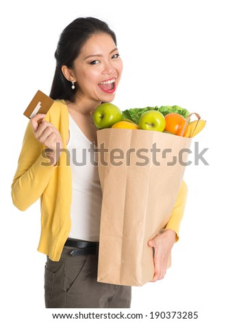 Happy young pan Asian woman holding paper shopping bag full of groceries and credit card isolated on white background. - stock photo