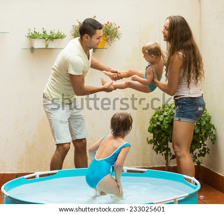 Happy young parents and little daughters having fun in pool outdoor. Focus on woman  - stock photo