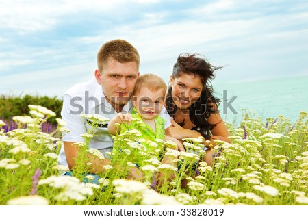Happy young parents and their son on hill