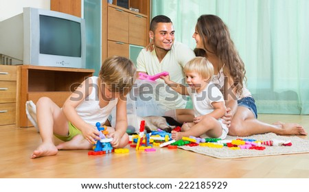 Happy young parents and two little daughters playing with plastic toys in home. Focus on man