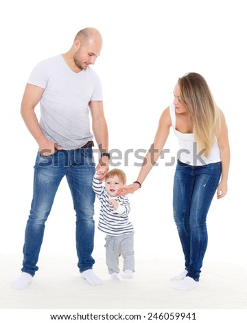 Happy young parents helping their little son doing the first steps.