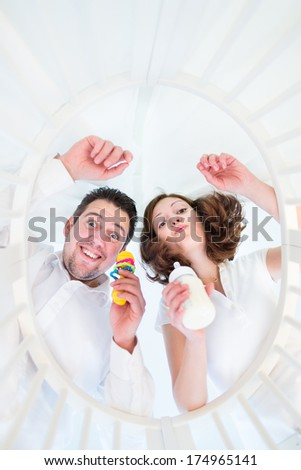 Happy young parents making funny faces looking at their baby in a white round crib - from baby perspective view - stock photo
