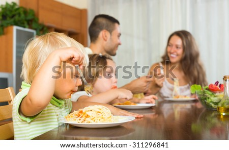 Happy young parents with children having lunch with spaghetti at home together. Focus on girl - stock photo