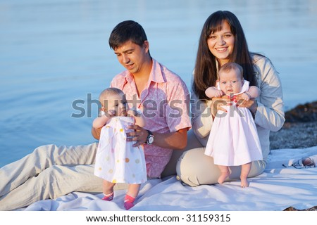 Happy young parents with infant children over sea