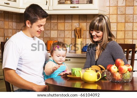 Happy young parents with their little daughter at kitchen