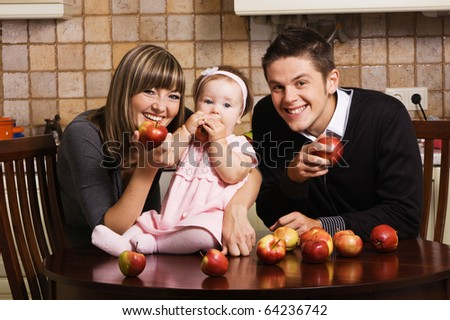 Happy young parents with their little daughter at kitchen with a lot of red apples