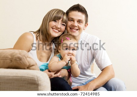 Happy young parents with their little daughter having fun at home - stock photo