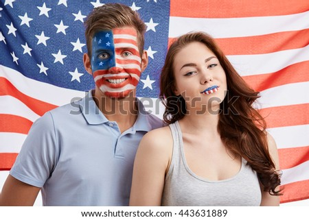 Happy young patriotic Americans with National make up celebrating Independence Day on 4th of July. American flag on the background, cute heterosexual couple