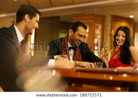 Happy young people behind gambling table with drinks - stock photo