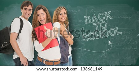 Happy young people by a blackboard with the words back to school