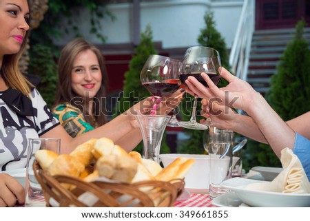 Happy young people celebrating and toasting with wineglasses in restaurant at lunch. - stock photo