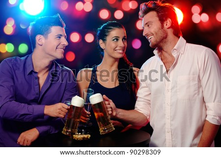 Happy young people clinking glasses at a party, smiling.? - stock photo