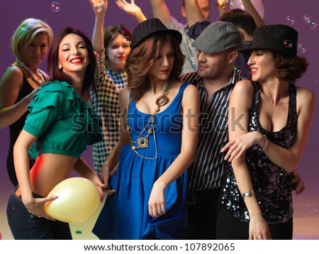 happy, young people flirting and dancing on the dancefloor, in a night club - stock photo