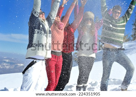 happy young people group have fun and enjoy fresh snow at beauti - stock photo