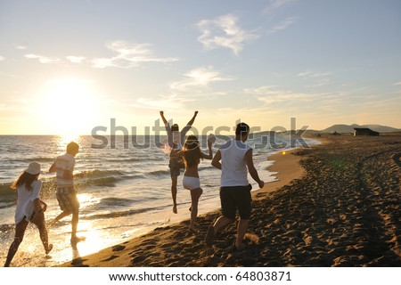 happy young people group have fun white running and jumping on beacz at sunset time - stock photo