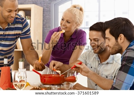 Happy young people having dinner together at home, eating cheese fondue, smiling. - stock photo
