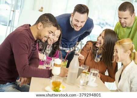 Happy young people having fun in a cafe - stock photo