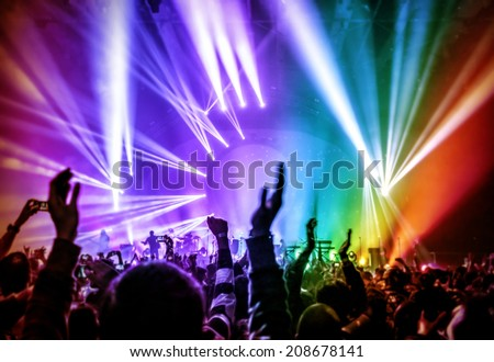 Happy young people having fun on rock concert in nightclub, colorful glowing lights, enjoying popular music, partying concept - stock photo