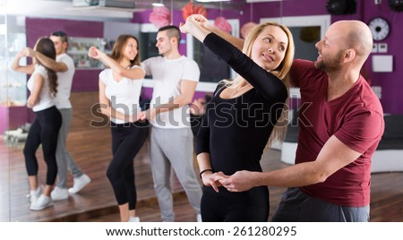 Happy young people having pasodoble dancing class indoors - stock photo