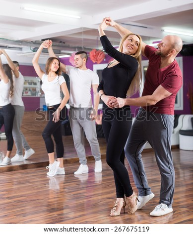 Happy young people having  rumba dancing class indoors - stock photo