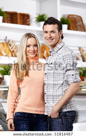Happy young people in food shop look in the chamber - stock photo