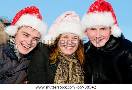 happy young people in red hats laughing in winter outdoors - stock photo