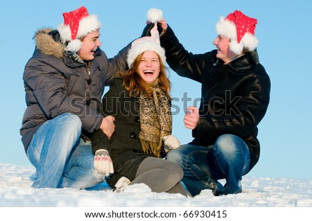 happy young people in red hats playing in snowy winter outdoors - stock photo