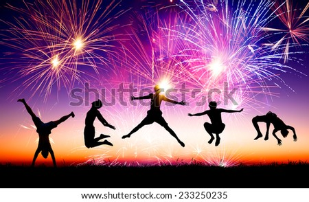 happy young people jumping on the hill with firework background - stock photo
