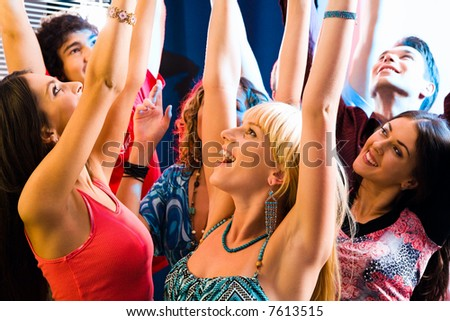 Happy young people lift up the hands at a party - stock photo