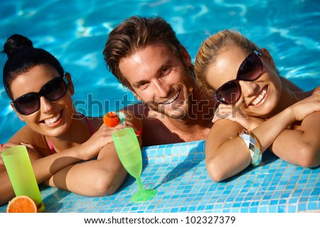 Happy young people on holiday, smiling in swimming pool. - stock photo