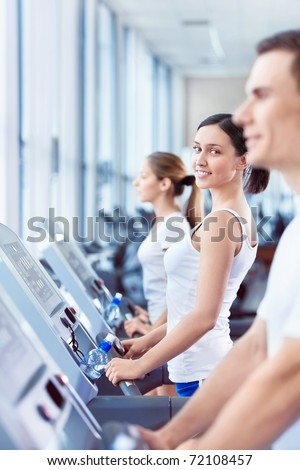 Happy young people on treadmills - stock photo