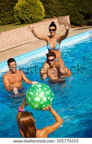 Happy young people playing in swimming pool, having fun. - stock photo