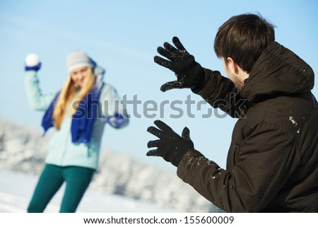 happy young people playing snowballs in sunny winter outdoors - stock photo