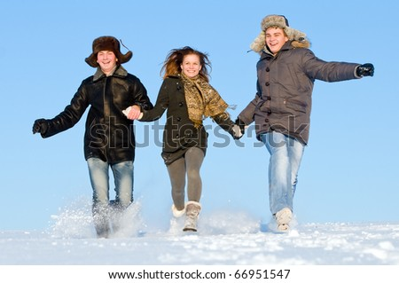 happy young people running with snow splashes in winter air - stock photo
