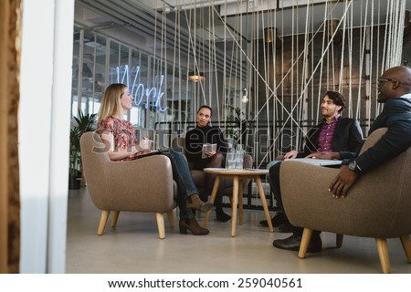 Happy young people sitting together in office discussing business. Office workers having a meeting in lobby. Diverse business people at startup. - stock photo
