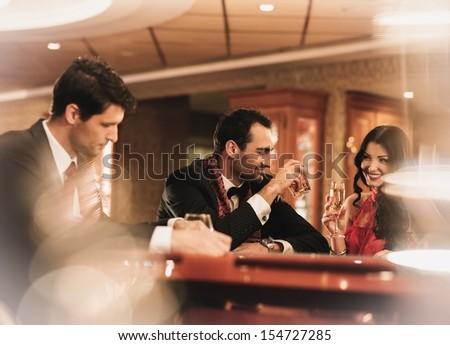 Happy young people sitting with drinks behind table  - stock photo