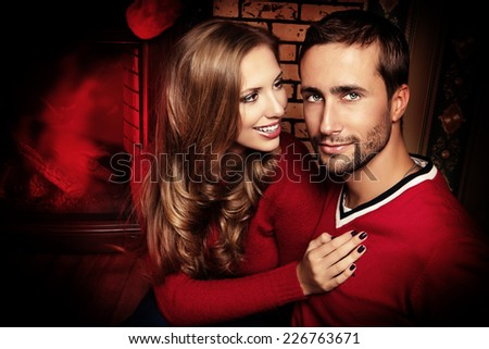 Happy young people spend a romantic evening by the fireplace. Christmas time. - stock photo