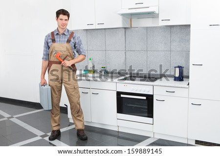 Happy Young Plumber Holding Pipe Wrench In Kitchen Room - stock photo
