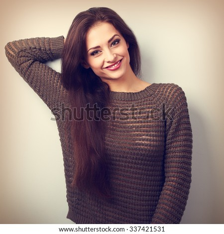 Happy young positive emotion brunette woman smiling in warm sweater. Vintage closeup toned portrait - stock photo