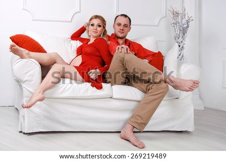 Happy young pregnant couple dressed in red embrace each other on a sofa in white living room. - stock photo