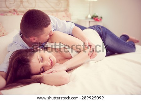 Happy young pregnant couple in bedroom at home
