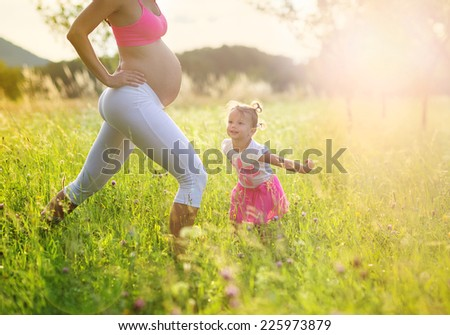 Happy young pregnant mother exercising with her little daughter in summer nature - stock photo