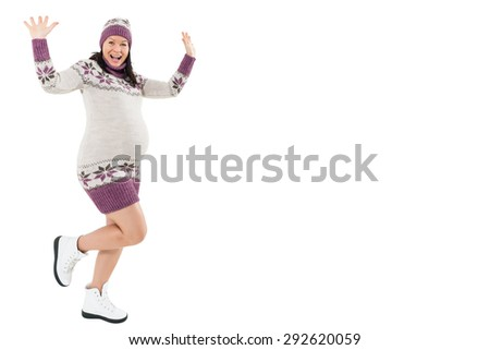 Happy, young pregnant woman dancing in a winter clothing on a white background.Copy space - stock photo
