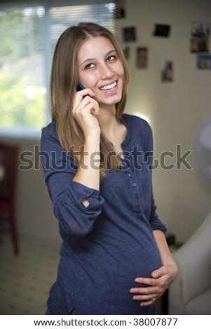 Happy young pregnant woman talking on t he phone at home.