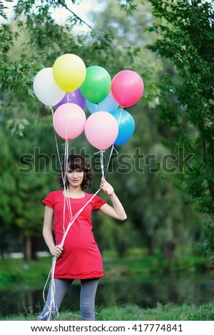 Happy young pregnant woman with balloons in the hands - stock photo