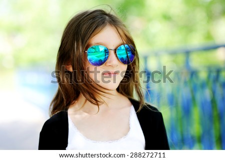 Happy young preteen brunette girl in sunglasses outdoors - stock photo