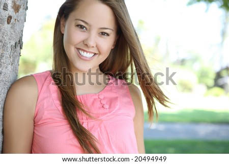 Happy young pretty female woman in the park relaxing - stock photo