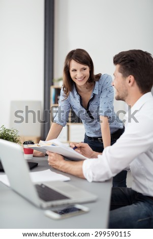 Happy Young Professional Couple Talking at the Table Inside the Office About the Documents. - stock photo