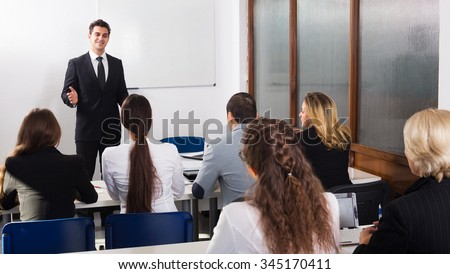 Happy young professor and professionals at extension business courses  - stock photo