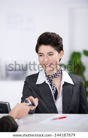 Happy young receptionist giving cardkey to customer at reception - stock photo